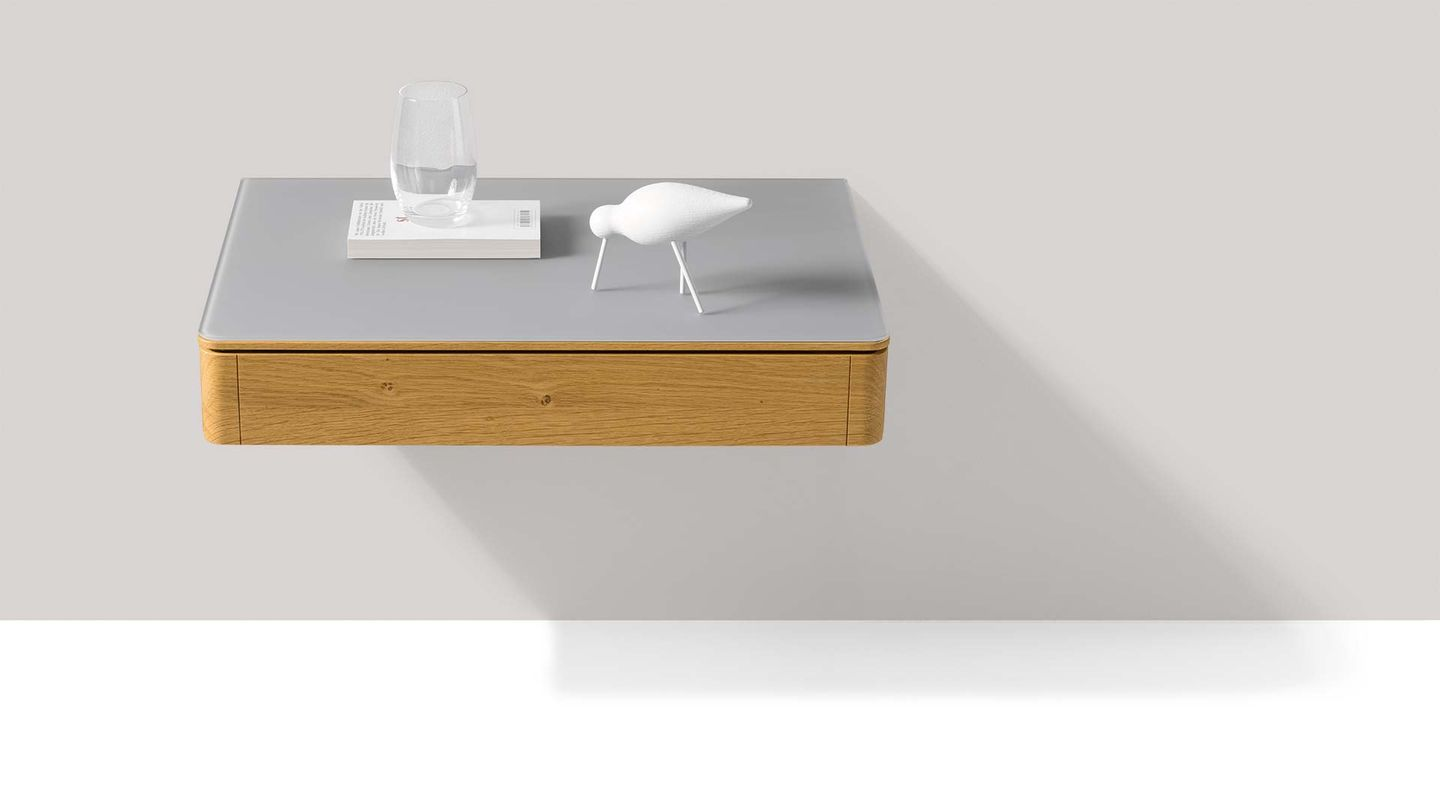 float bedside cabinet made of wood with glass surface hanging