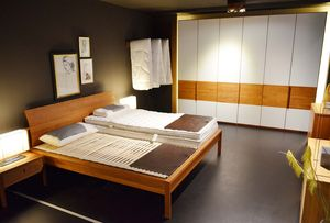 Solid wood bed with mattress at TEAM 7 in Munich