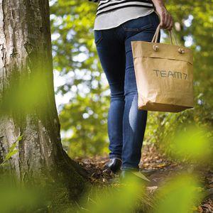 Person im Wald mit TEAM 7 Tüte