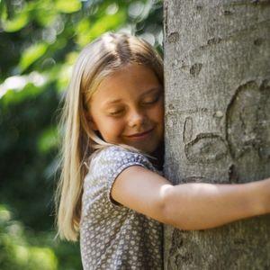 Bambina che abbraccia albero